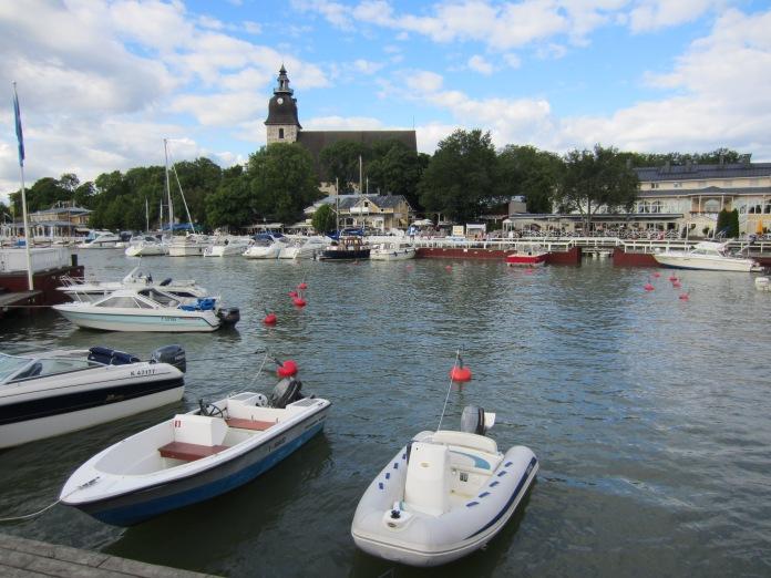 Naantalin ranta on viehättävää aluetta veneineen ja ravintoloineen. Taustalla näkyy Naantalin kirkko.