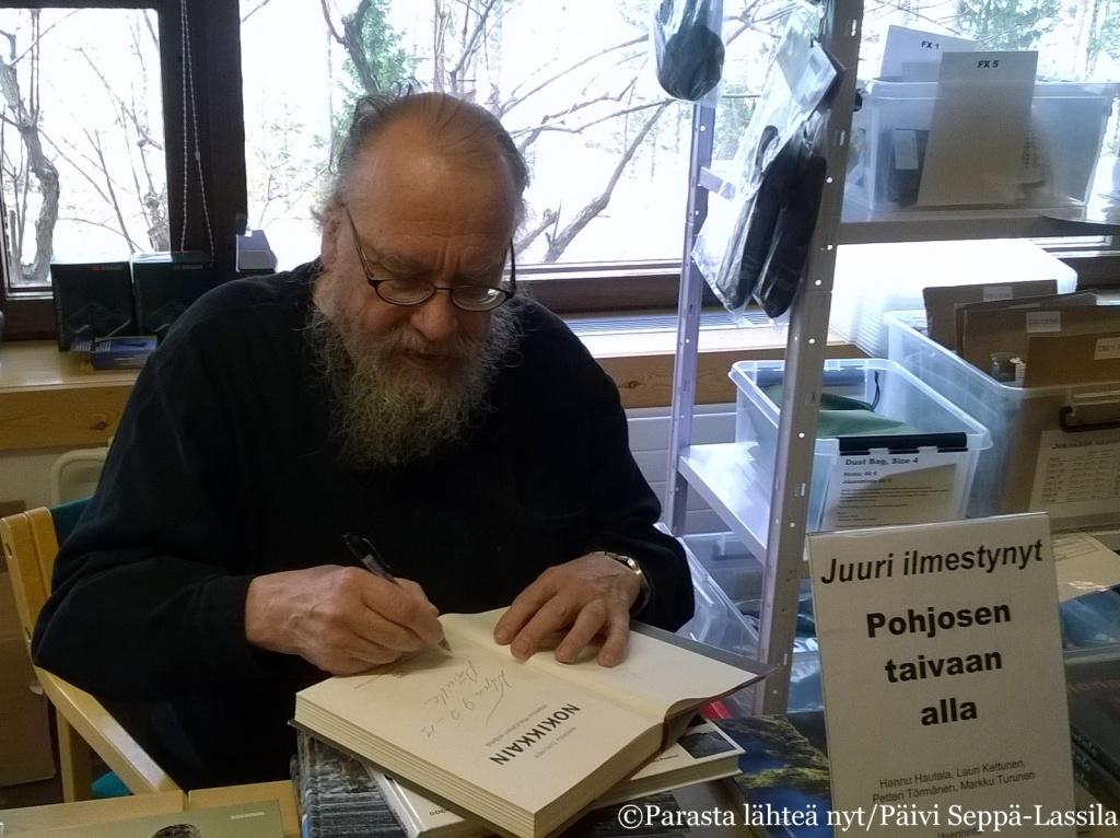 Hannu Hautala signeeraa kirjaansa Nokikkain Suomen Luonnonvalokuvaajien Syyspäivillä.