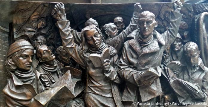 Yksityiskohta Paul Dayn The Meeting Place -patsaan friisistä St Pancras -asemalta.