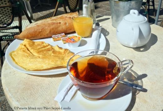 Aamiainen nizzalaisen tapaan: patonkia, tuoremehua, teetä ja munakas.