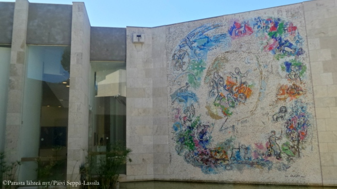 Yhdestä huoneesta on näkymä vesialtaalle, jonka takana on Chagallin mosaiikkiteos
