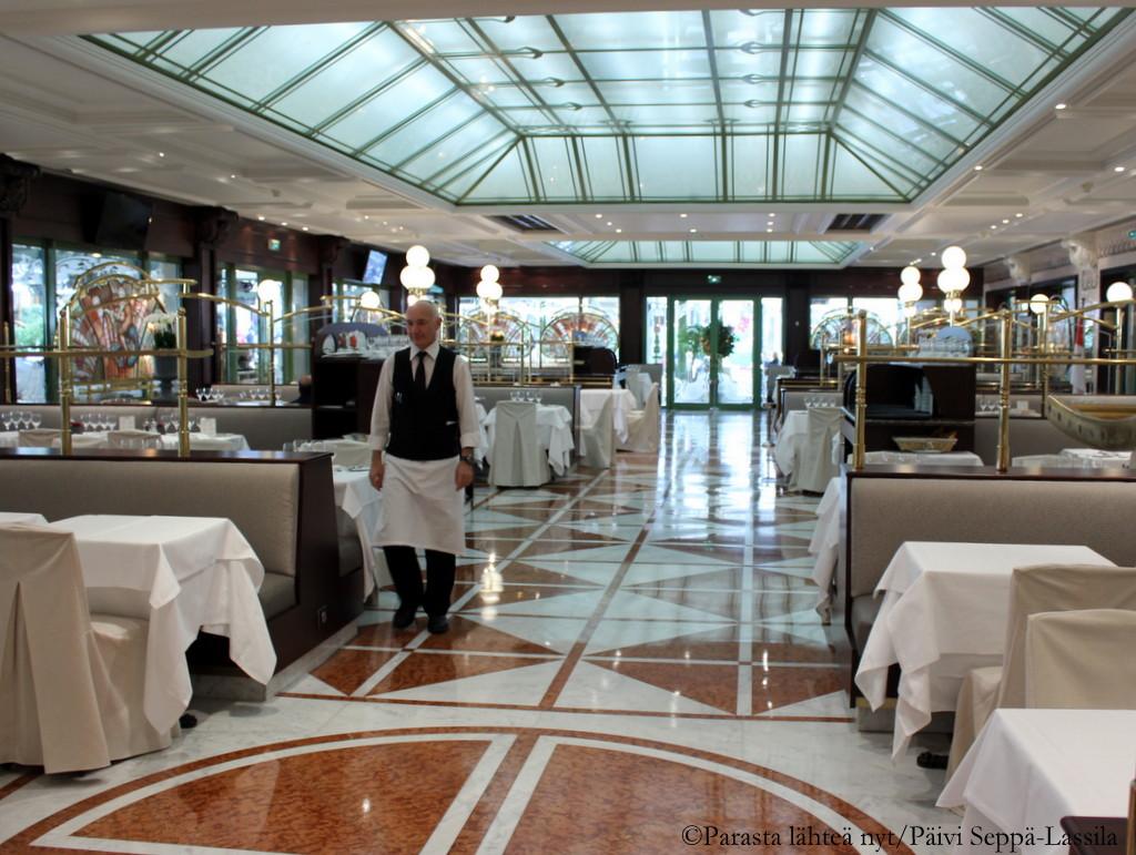 Cafe de Parisin sisätiloja. Asiakkaat viihtyivät aurinkoisena päivänä ravintolan terassilla.
