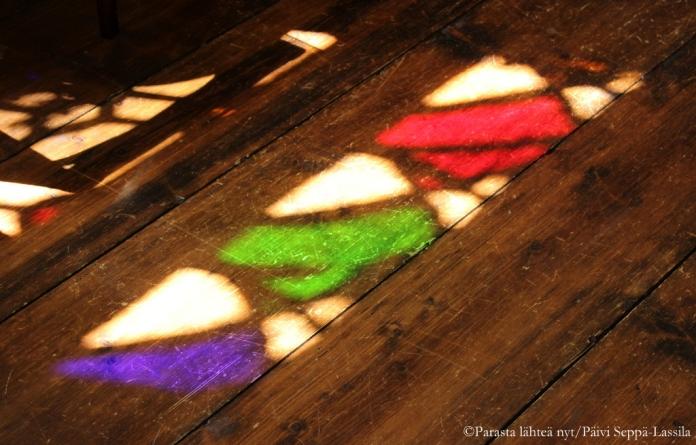 Ikkonoiden värilliset lasipalaset heijastuivat tummaan puulattiaan.