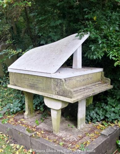 Flyygelin muotoinen hautamuistomerkki. Päädyssä lukee Thornton ja etuosassa on Puccinin mietelause.
