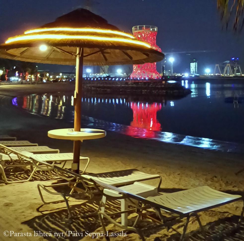 Uimarantaa Abu Dhabissa joulunaikaan iltavalaistuksessa. Taustalla näkyy punaisella valaistuksella koristeltu näkötorni.