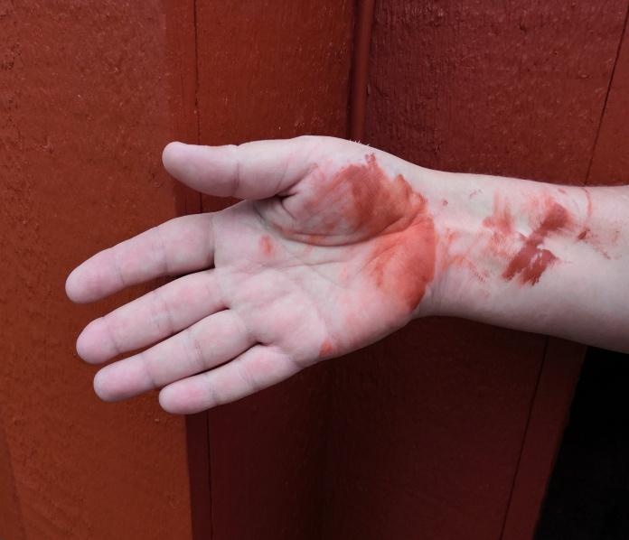 Punainen seinä, käsi, jossa on punaista maalia