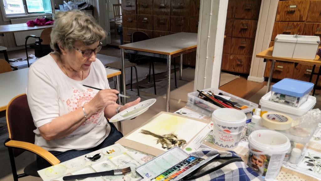 Nainen maalaamassa lautasta posliinivärein.