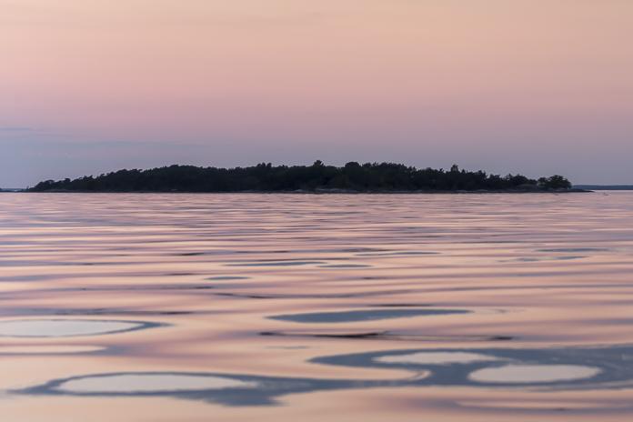 Meri vaaleanpunaisena auringonlaskun aikaan