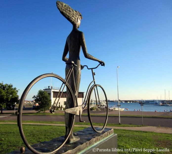 Patsas, nainen taluttaa polkupyörää