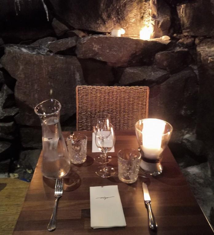 Ravintolapöytä, kynttilöitä, kivistä muurattu seinä
