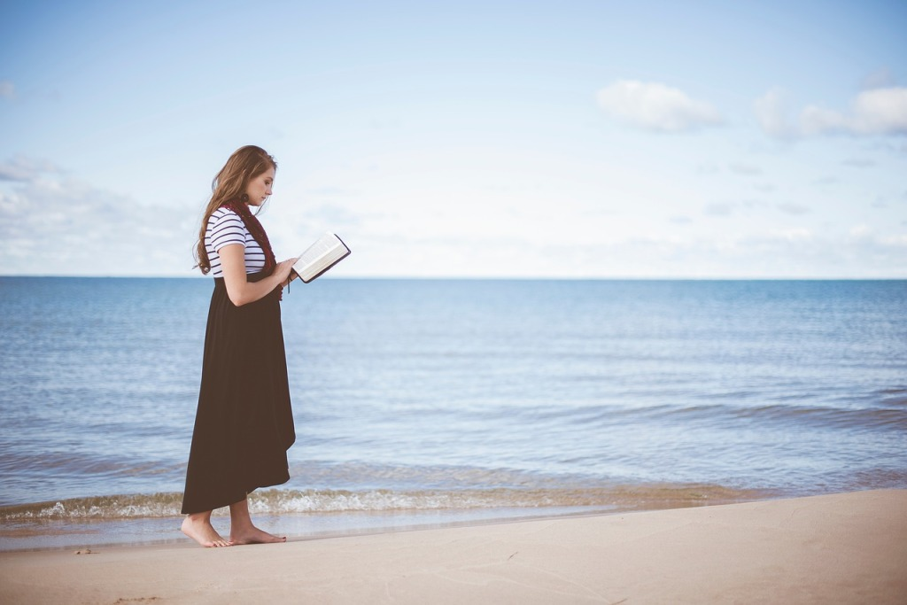 Nuori nainen hiekkarannalla lukemassa kirjaa.