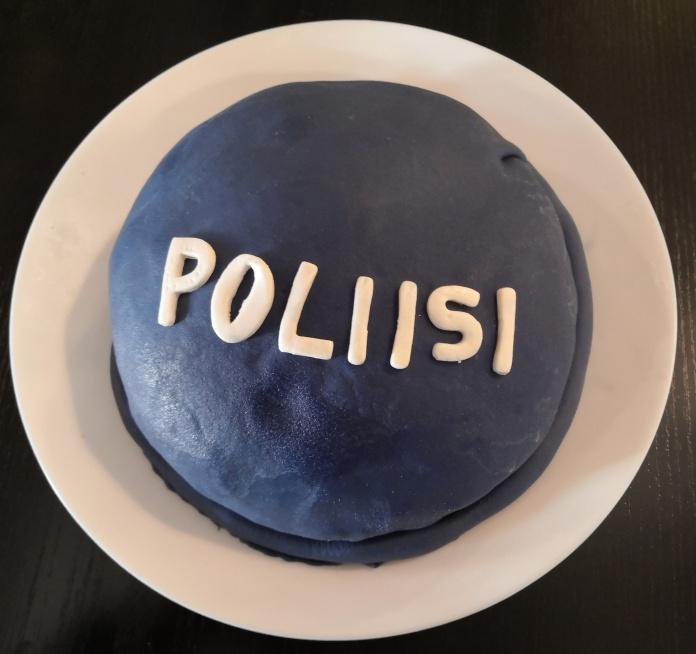 Sinisellä päällystetty kakku, jossa on teksti Poliisi.