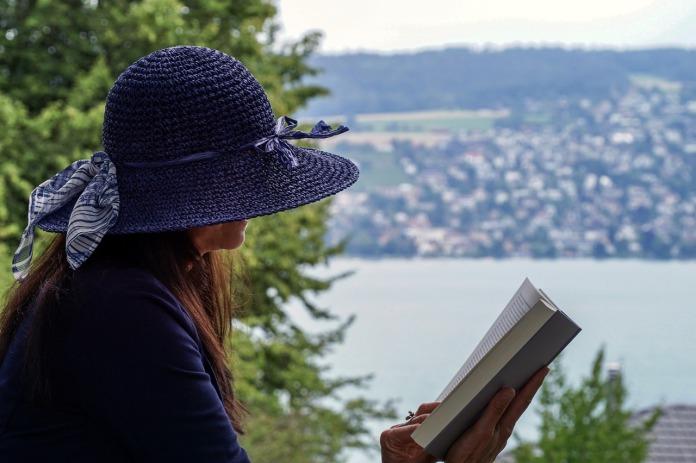 Lierihattuinen nainen lukee kirjaa, takana järvimaisema.