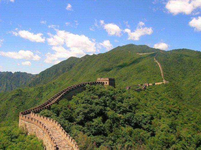 Kiinan muuri, vihreää metsää ja sinistä taivasta valkoisine pilvineen
